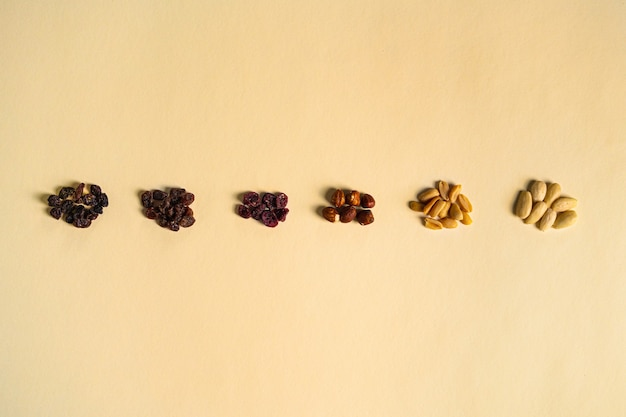 Mix van noten en gedroogde vruchten gescheiden door type en kleur op een gele achtergrond. rozijnen, gedroogde berberis, hazelnoten, pinda's en amandelen.