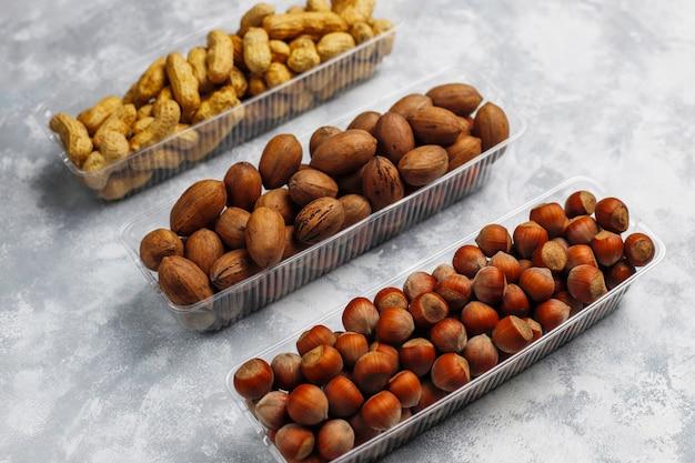 Mix van noten in kleine plastic platen op beton, bovenaanzicht.