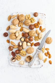 Mix van noten - walnoot, amandelen, pecannoten, macadamia en mes voor het openen van de schaal op witte houten snijplank.
