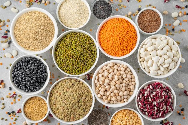 Mix van peulvruchten, kikkererwten, linzen, bonen, erwten, quinoa, sesam, chia, lijnzaad in kommen op een grijze betonnen achtergrond. gezond, veganistisch en glutenvrij eten. bovenaanzicht.