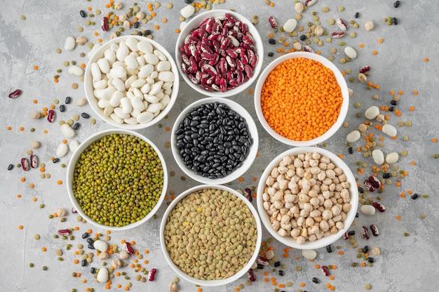 Mix van peulvruchten, kikkererwten, linzen, bonen in kommen op een grijze betonnen ondergrond. gezond, veganistisch en glutenvrij eten. bovenaanzicht. ruimte kopiëren.