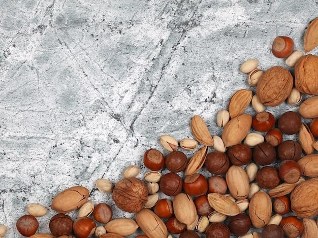 Mix van rauwe inshell noten op grijze stenen achtergrond. bovenaanzicht met kopieerruimte