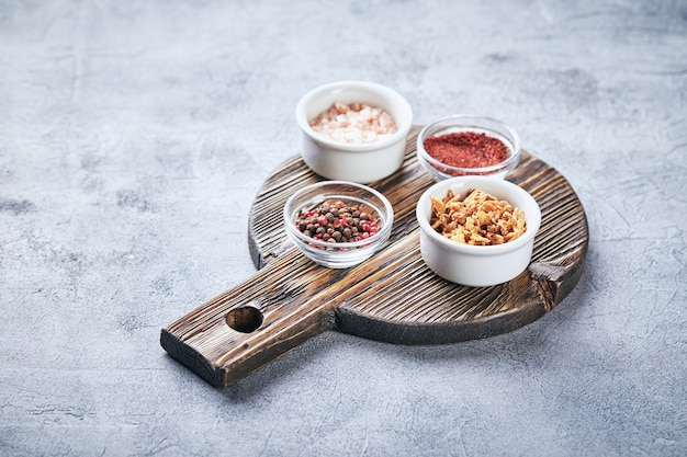 Mix van rode en zwarte peperkorrels, grof roze himalayazout, gedroogde tomaten en gedroogde uien in kleine kommetjes