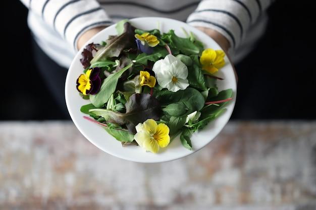 Mix van salades met bloemen op een witte plaat gehouden door een meisje