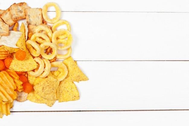 Mix van snacks: pretzels, crackers, chips en nacho's op tafel