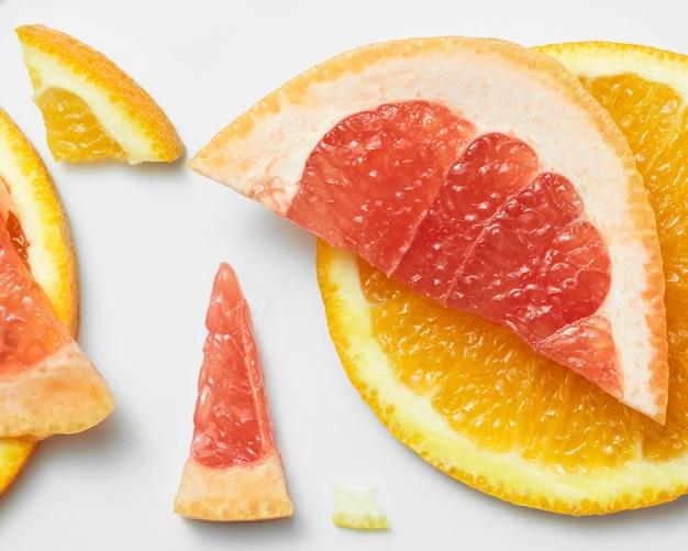 Mix van vers gesneden sinaasappelen en grapefruits op een witte ondergrond