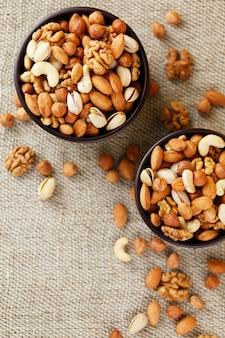 Mix van verschillende noten in een houten beker tegen de stof van jute. noten als structuur en achtergrond, macro. bovenaanzicht