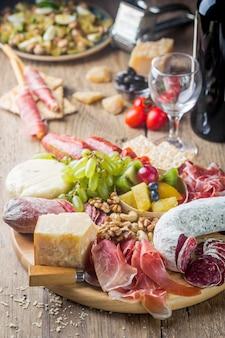Mix van verschillende snacks en hapjes. spaanse tapas of italiaanse wijn die op een houten plaat wordt geplaatst
