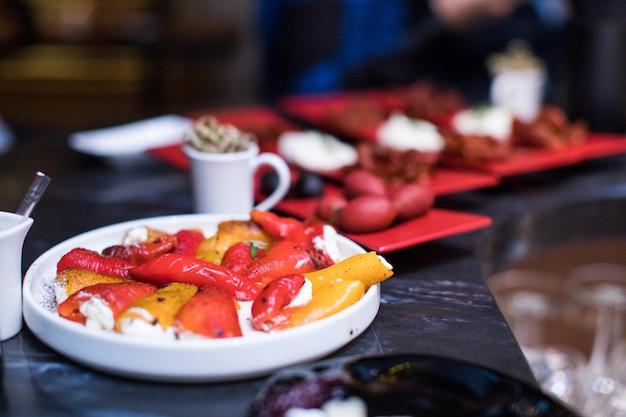 Mix van verschillende snacks en hapjes. spaanse tapas op een zwarte stenen ruimte. bar. ruimte voor tekst. deli, sandwiches, olijven, worst, ansjovis, kaas, jam, paprika, tomaten. bovenaanzicht