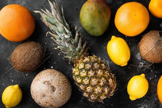 Mix van verschillende soorten fruit, op zwarte donkere stenen tafelachtergrond, bovenaanzicht plat gelegd