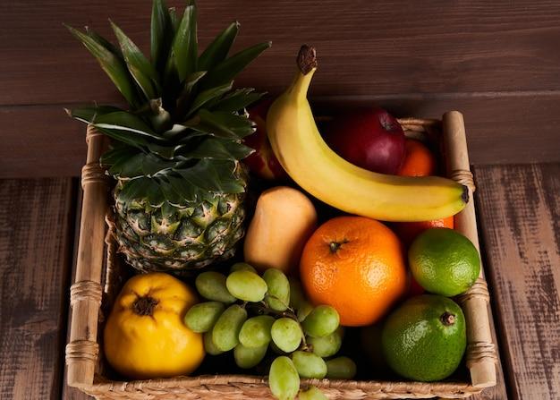 Mix van verse, sappige kleurrijke exotische tropische vruchten in mand op houten achtergrond bovenaanzicht