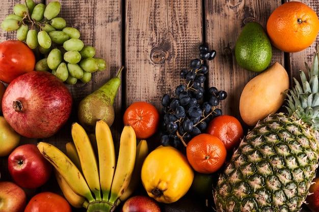 Mix van verse, sappige kleurrijke exotische tropische vruchten op houten achtergrond bovenaanzicht met kopieerruimte