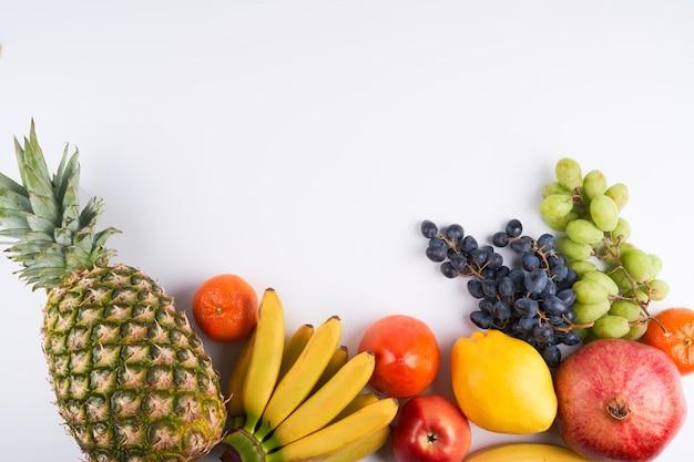 Mix van verse, sappige kleurrijke exotische tropische vruchten op witte achtergrond bovenaanzicht met kopie ruimte