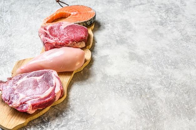 Mix van vlees rauwe steaks zalm, rundvlees, varkensvlees en kip. grijze achtergrond. bovenaanzicht.