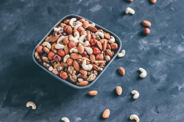Mix van walnoten, cashewnoten, hazelnoten en amandelen in een keramische kom op een blauwe betonnen achtergrond in donkere stijl