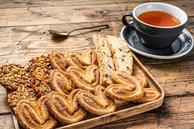 Mix van zoete koekjes met een kopje thee. houten achtergrond. bovenaanzicht.