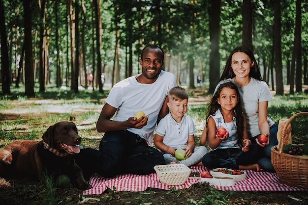Mixed race family picknicken met gezonde voeding