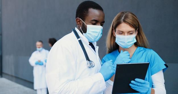 Mixed-races paar, man en vrouw, artsen in medische maskers praten en tablet-apparaat gebruiken. multi-etnische mannelijke en vrouwelijke artsen die op gadgetcomputer tikken en scrollen. coworking in het ziekenhuis.