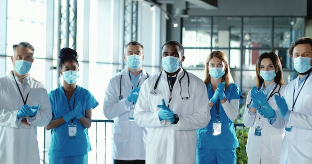 Mixed-races team van mannelijke en vrouwelijke artsen applaudisseren in het ziekenhuis. internationale groep medici in medische maskers. beschermde werknemers. multi-etnische artsen en verpleegsters in uniformen in kliniek applaus