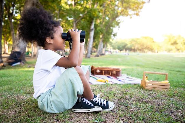 Mixedrace meisje op zoek natuurlijk en met behulp van een verrekijker in openbaar park met een blij gezicht staan en glimlachen concept van natuur- en wildstudies