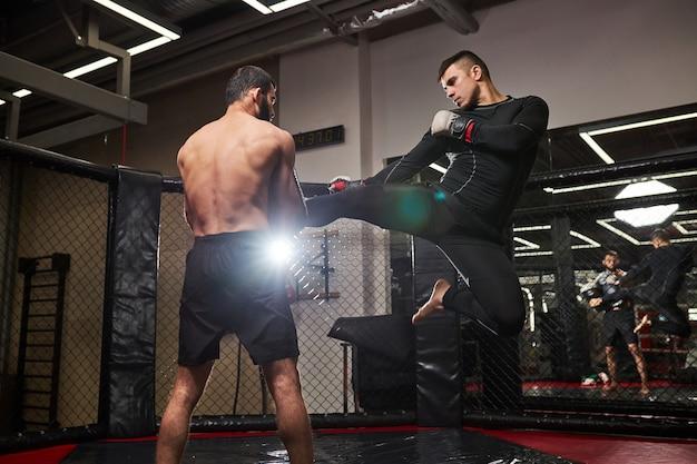 Mma. twee professionele boksers boksen, fit gespierde blanke atleten vechten. sport, competitie, opwinding en menselijke emoties concept. zijaanzicht op mannen in beweging. vechten zonder regels