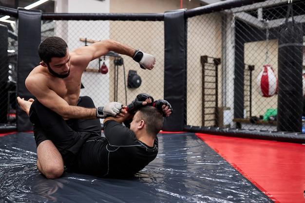 Mma. twee professionele boksers boksen, fit gespierde blanke atleten vechten. sport, competitie, opwinding en menselijke emoties concept Premium Foto