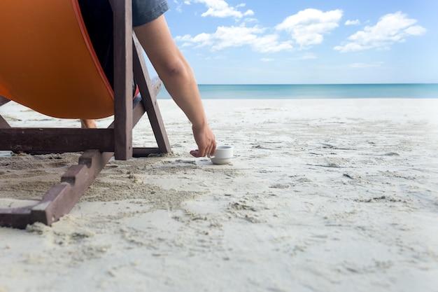 Mn zittend op een strandstoel en koffie drinken aan het strand