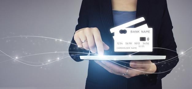 Mobiel bankieren netwerk, online betaling, digitale marketing. witte tablet in onderneemsterhand met digitaal hologram virtueel creditcardteken op grijze achtergrond. online bankieren op touchscreen.