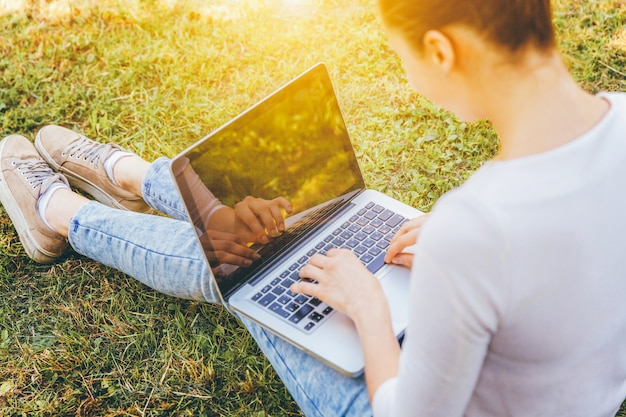 Mobiel kantoor. freelance bedrijfsconcept. jonge vrouwenzitting op groen grasgazon in stadspark dat aan laptop pc-computer werkt. meisje van de levensstijl het authentieke spontane student in openlucht bestuderen.