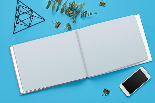 Mobiel met zwart scherm, leeg open notitieboekje, vier bindklemmen, ijzeren beeldje van driehoek met kubus