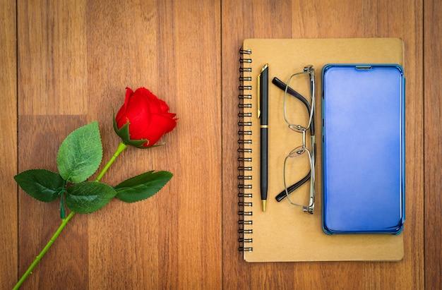 Mobiel op kladblok en rode roos op houten tafel