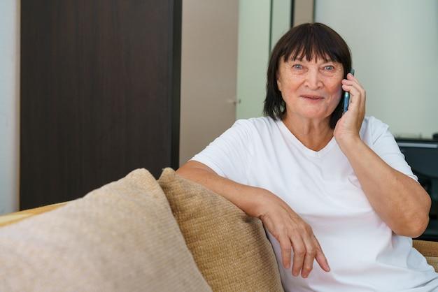 Mobiel portret van vrolijke blanke grootmoeder die met familie belt terwijl ze op de bank zit in mod...