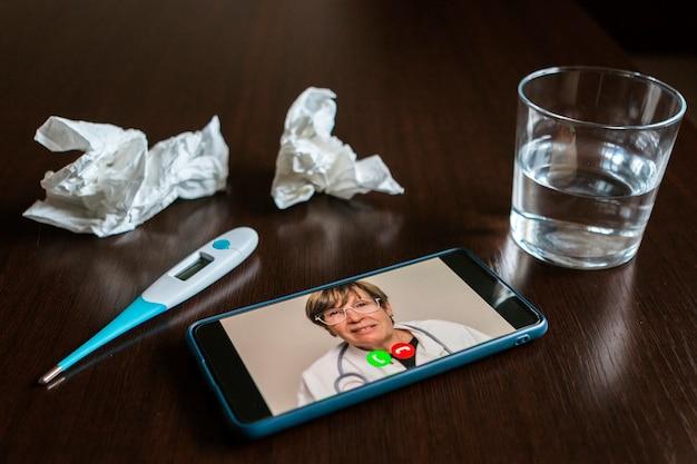 Mobiel scherm met een mannelijke dokter online, wat tissues, een glas water en thermometer boven een tafel.