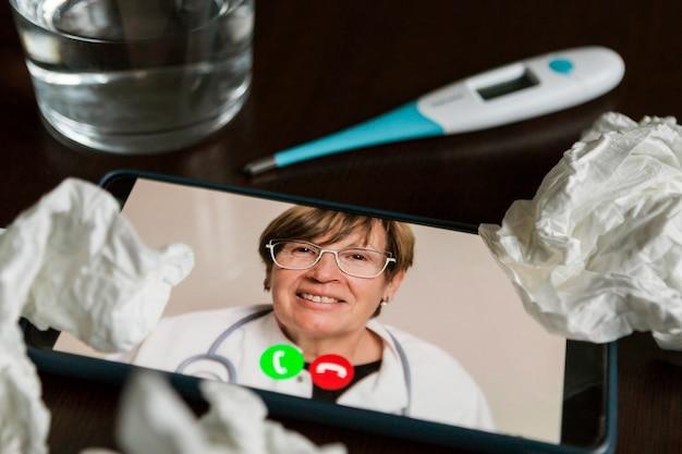 Mobiel scherm met een senior arts die een online consult heeft, wat tissues, een glas water en een thermometer boven een tafel.