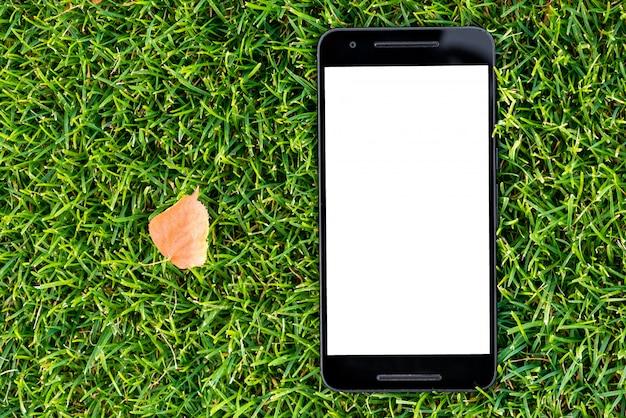 Mobiel slim telefoonmodel met het witte scherm op groene grasachtergrond en de herfst geel le