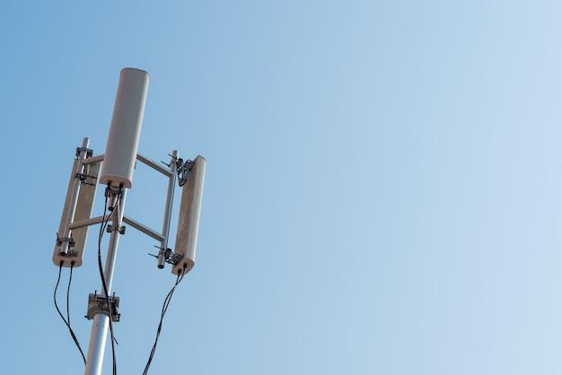 Mobiele antenne en blauwe hemel.
