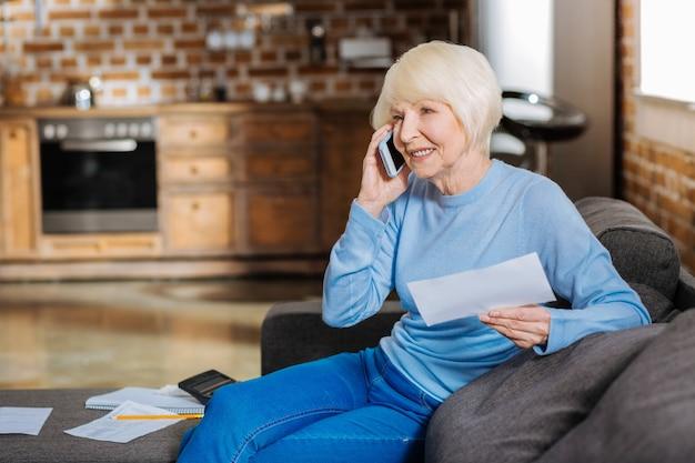 Mobiele communicatie. leuke aangename oude vrouw die haar mobiele telefoon vasthoudt en glimlacht terwijl ze aan de telefoon spreekt