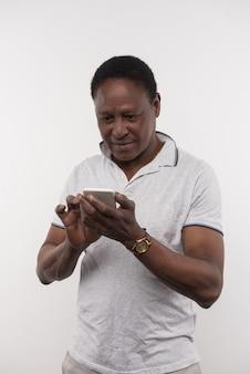 Mobiele gadget. aardige, aangename man die naar zijn smartphonescherm kijkt terwijl hij nieuws controleert