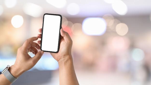 Mobiele slimme telefoon in de hand van de mens bij het bureauwerk.