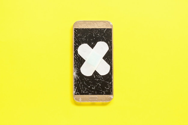 Mobiele smartphone met gebarsten scherm bevestigd met gips op geel