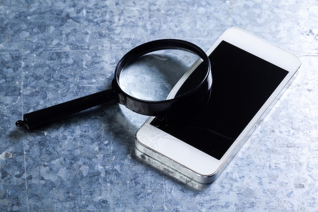 Mobiele smartphone, vergrootglas. bovenaanzicht