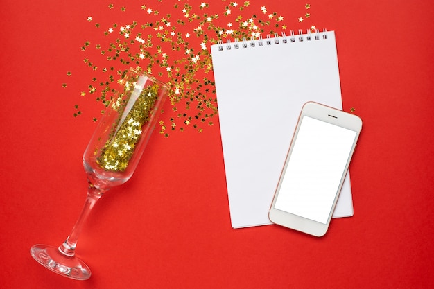 Mobiele telefoon, blocnote en champagneglazen met gouden sterrenconfettien, kerstmis en nieuw jaarconcept