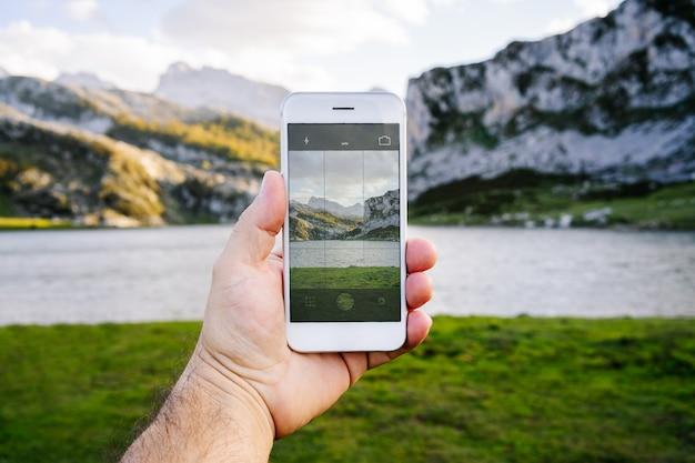 Mobiele telefoon die een foto van een berglandschap maakt