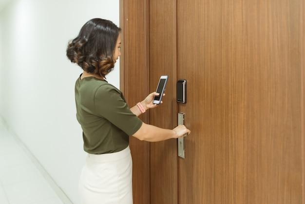 Mobiele telefoon die wordt gebruikt voor het openen van de veiligheidsdeur van haar huis