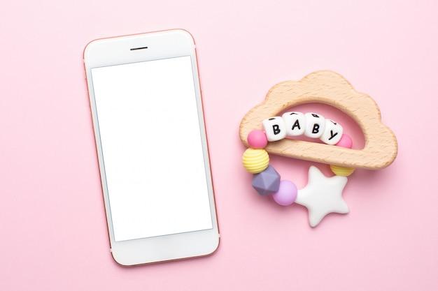 Mobiele telefoon en baby houten rammelaars en speelgoed op roze