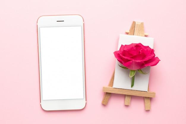 Mobiele telefoon en canvas voor het schilderen met roze bloem op roze