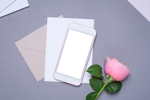Mobiele telefoon en envelop met roze roos op grijs