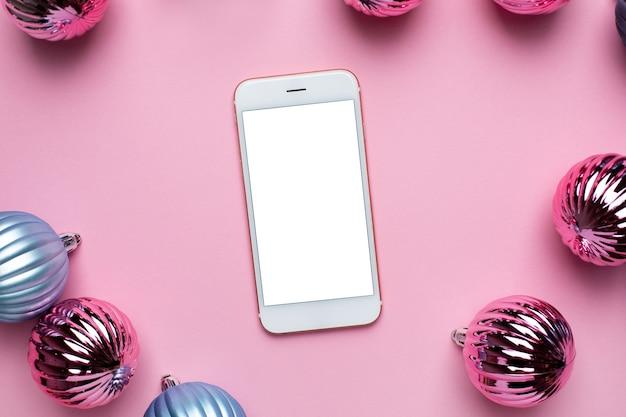 Mobiele telefoon en glanzende blauwe en roze kerstballen voor decoratie op roze achtergrond bovenaanzicht