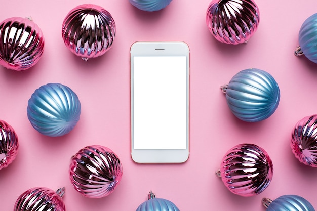 Mobiele telefoon en glanzende blauwe en roze kerstballen voor decoratie op roze achtergrond, nieuwe jaarbal