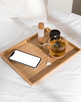 Mobiele telefoon en glas thee op bed